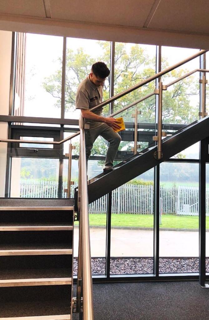 Staff cleaning glass stairway in commercial premises
